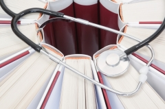 Set of encyclopedias, books and stethoscope closeup.